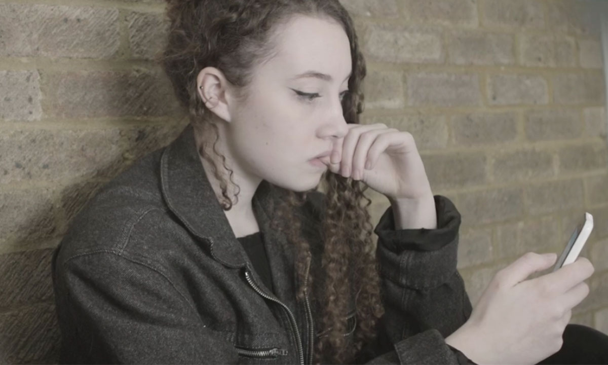 Teenage girl using her phone and looking worried