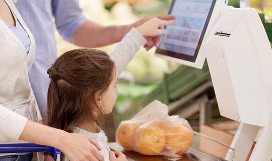 A young girl helping her mother at a self-service till in a supermarket