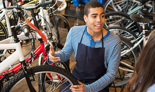 A teenage boy working in a bike shop