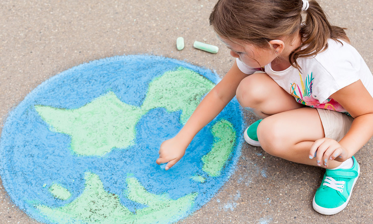 Young girl draws the world with chalk on the ground