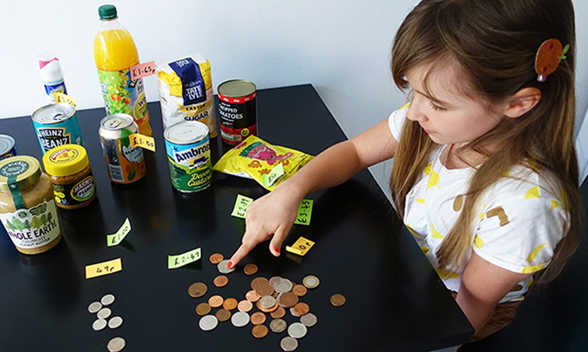 A young girl counts change and compares the prices of supermarket items