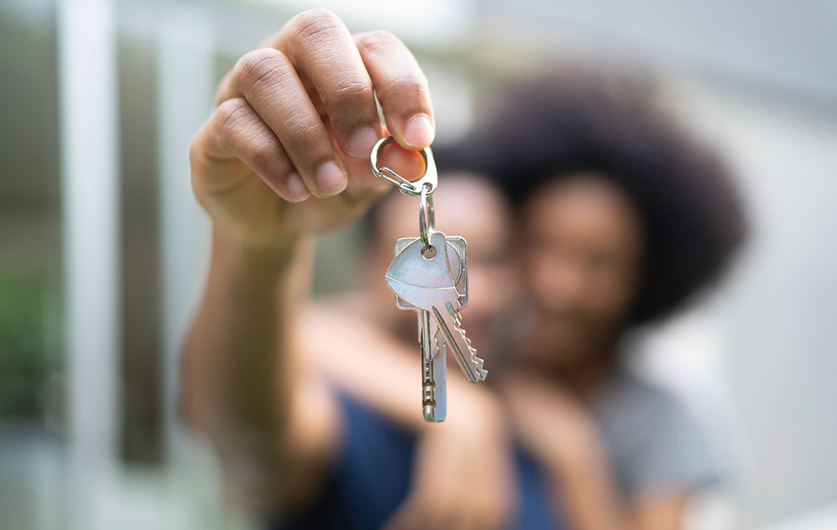 Happy homeowners hold up keys to their new home